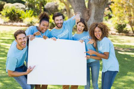 hoja en blanco: Grupo de voluntarios que sostiene una hoja en blanco y apuntando a él en el parque Foto de archivo