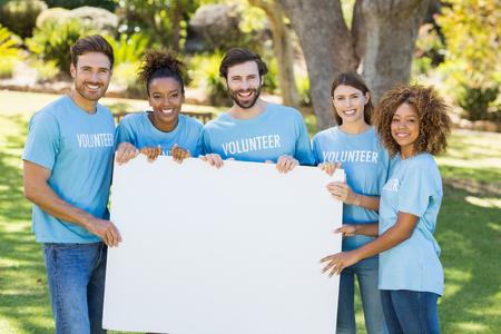hoja en blanco: Retrato de grupo de voluntarios que sostiene la hoja en blanco en el parque