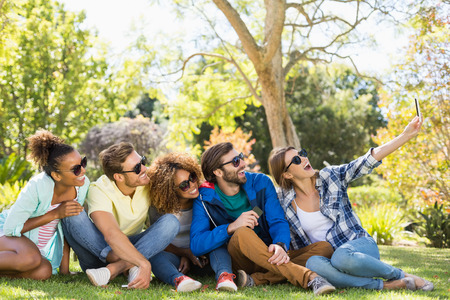 in loving memory: Group of friends taking a selfie with the mobile phone in park Stock Photo