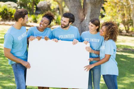 hoja en blanco: Grupo de voluntarios que sostiene la hoja en blanco en el parque Foto de archivo