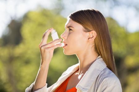 inhaler: Woman using asthma inhaler in a park