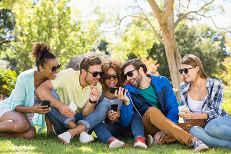 Group of friends using mobile phone in park