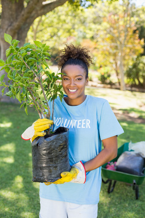 Portrait of volunteer woman holding plant in park Stock Photo