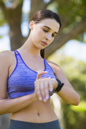 checking time: Woman checking time while exercising in park