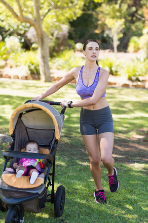 baby stroller: Young woman walking with baby stroller in park Stock Photo