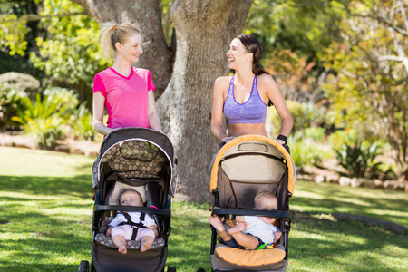 baby stroller: Women standing with the baby stroller in park