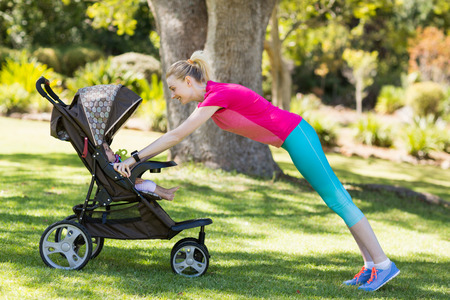 baby stroller: Woman exercising with baby stroller in park