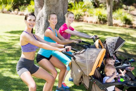 Ženy vykonávají s dítětem kočárku v parku