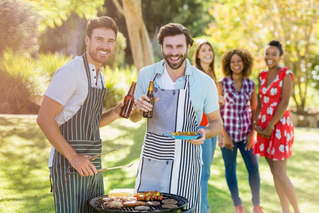 barbecue grill: Two men holding a beer bottle while preparing barbecue grill in park and friends in background Stock Photo