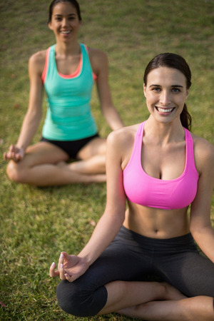 Portrait of beautiful women sitting on grass and doing meditation in park