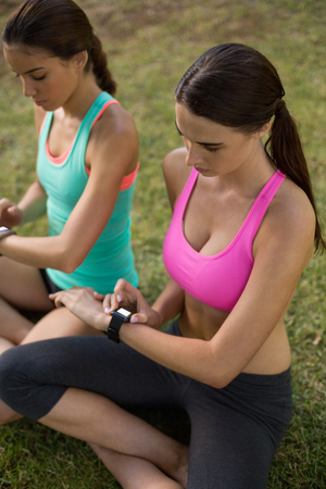 adjusting: Beautiful women adjusting a time on wristwatch in park Stock Photo