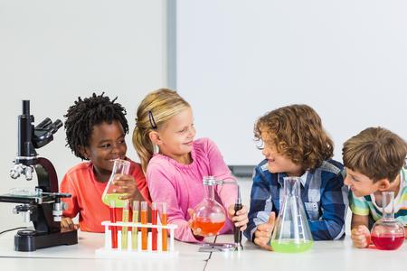 Niños haciendo un experimento químico en el laboratorio en la escuela