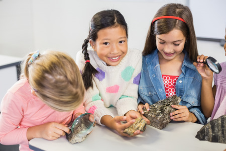 specimen: Group of kids looking at specimen stone through magnifying glass in classroom