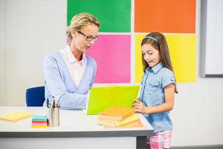 Enseignant aider écolière dessin à l'école