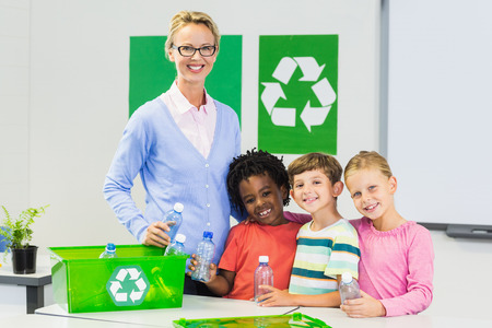 recycle logo: Portrait of teacher and kids standing in classroom with recycle logo