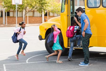 Boldog tanár adja a magas öt gyerek beírása közben az autóbusz Stock fotó