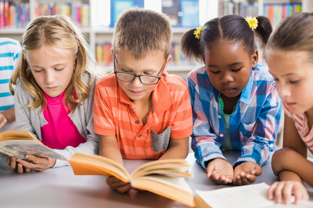Kids reading a book in library at school Stock Photo