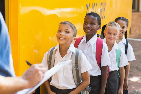 Teacher updating check list of kids while entering in bus Imagens