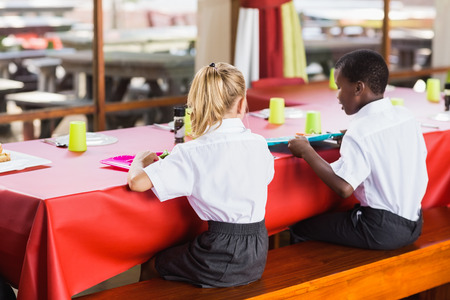 school cafeteria: Rear view of boy and girl in school uniforms having lunch in school cafeteria