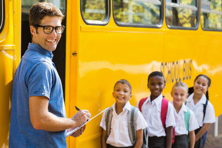 Portrait of teacher updating check list of kids while entering in bus