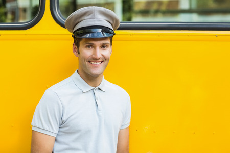 driver cap: Portrait of bus driver smiling in front of bus Stock Photo