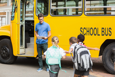 Smiling teacher updating check list of kids while entering in bus Imagens