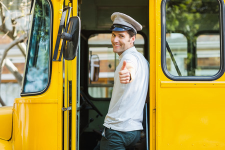 the entering: Portrait of bus driver showing thumbs up while entering in bus
