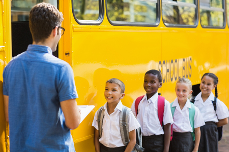 check list: Teacher updating check list of kids while entering in bus