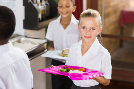 school cafeteria: Portrait of schoolgirl holding food tray in school cafeteria