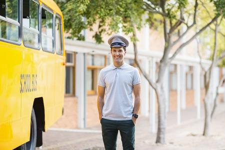 bus driver: Retrato de la sonrisa conductor del autob�s de pie con las manos en el bolsillo en frente del autob�s