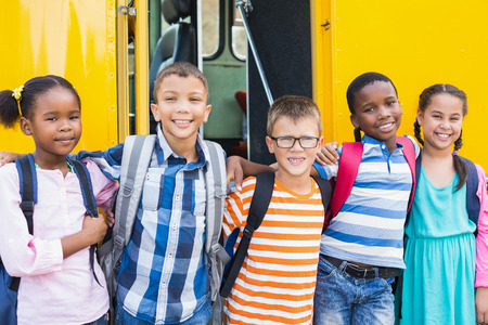 arm around: Portrait of smiling kids standing with arm around in front of school bus
