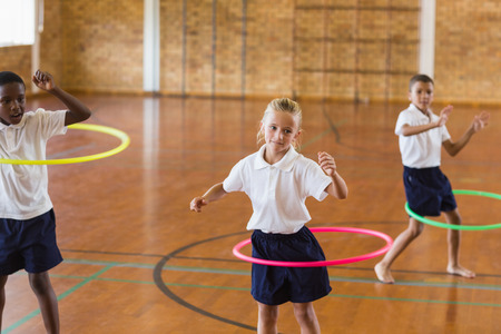 school gym: Students playing with ring in school gym at elementary school Stock Photo