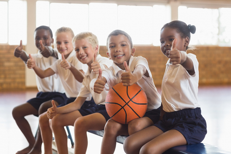 Lachende studenten met basketbal zien thumbs up in school gym