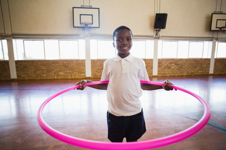 school gym: Portrait of smiling boy playing with ring in school gym Stock Photo
