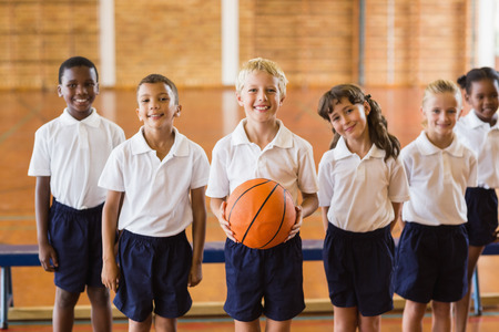 school gym: Portrait of smiling students standing with basketball in school gym Stock Photo
