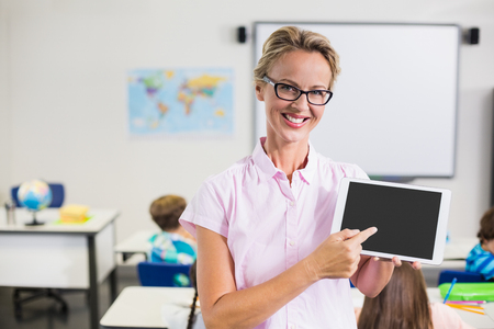 early 40s: Portrait of teacher pointing at the digital tablet in classroom Stock Photo