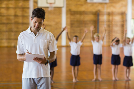 school gym: Sports teacher writing notes on clipboard while students exercising in school gym
