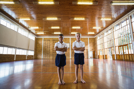 lass: Boys standing with arms crossed in basketball court of school gym