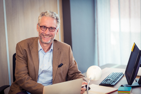mature business man: Portrait of businessman smiling in office Stock Photo