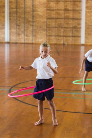 school gym: Schoolgirl playing with ring in school gym at elementary school
