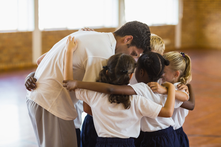 educator: Sport teacher and students forming a huddle in school gym