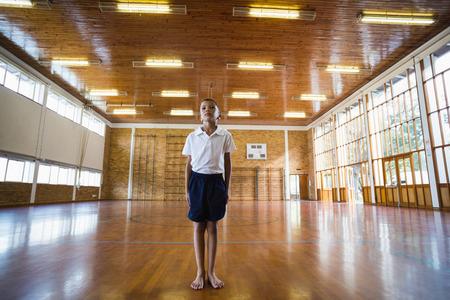 school gym: Boy standing in basketball court of school gym Stock Photo