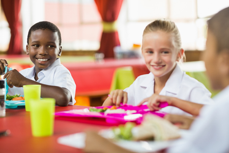 Happy children having lunch during break time in school cafeteria Standard-Bild
