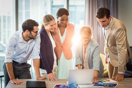 people interacting: Group of business people interacting using laptop in the office Stock Photo