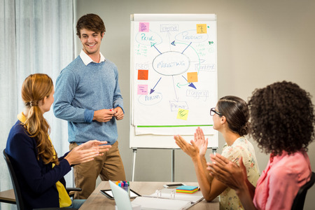 applauding: Coworkers applauding a colleague after presentation in the office Stock Photo