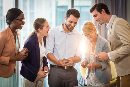 사무실에서 휴대 전화를 사용하여 상호 작용하는 비즈니스 사람의 그룹 스톡 콘텐츠