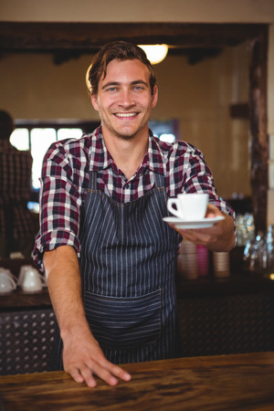 handing over: Waiter handing over a coffee in a restaurant Stock Photo