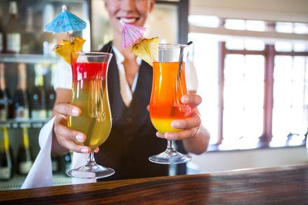 handing over: Waitress handing over cocktails in a restaurant Stock Photo