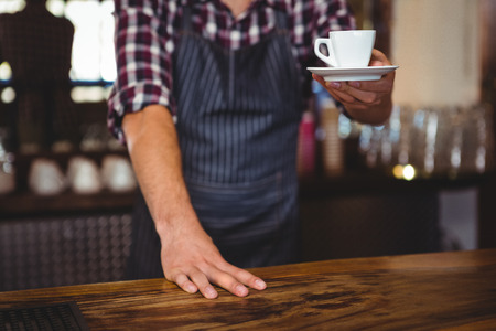 over the counter: Waiter handing over a coffee in a restaurant Stock Photo