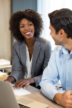 people interacting: Smiling business people interacting with each other in office Stock Photo